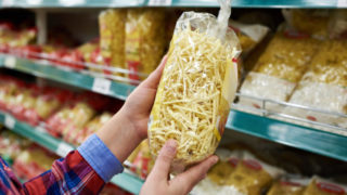 Buyer with package pasta in shop